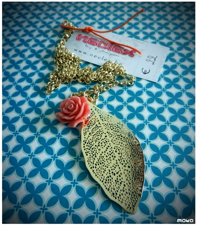 Gouden filigree blad met roze koraalroos